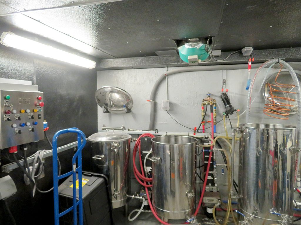 Overview of a one-barrel brewhouse with two kettles next to a large brewpot.