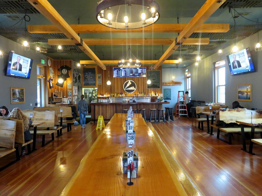 Overview of a large dining space with a bar at the end of the space at Ridgewalker Brewing.