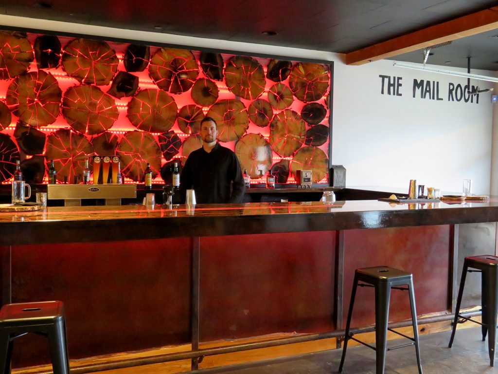 Overview of a bar with a red light background behind multiple tree rings with a man standing behind the bar at Ridgewalker Brewing's The Mail Room event space.