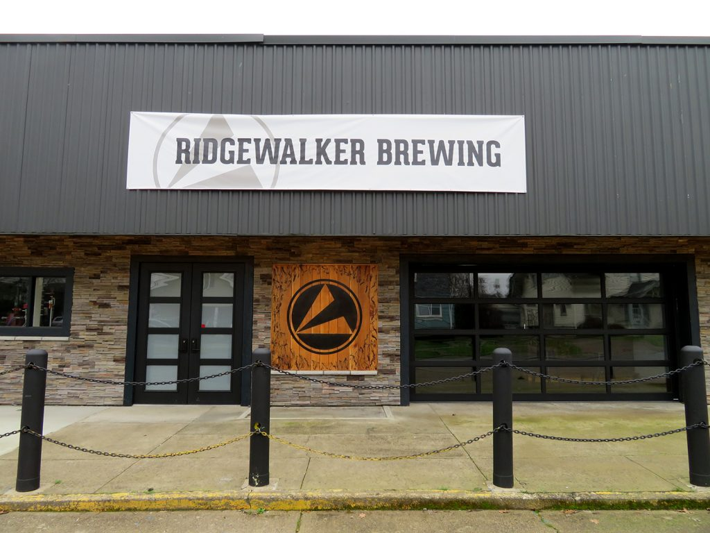 "Exterior overview of a former U.S. Post Office building with a banner above it that says ""Ridgewalker Brewing."""