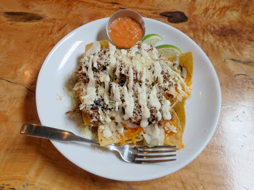 A circular white plate with tortilla chips covered with cheddar cheese, shredded beef, queso fresco, and other toppings to make a loaded plate of nachos.