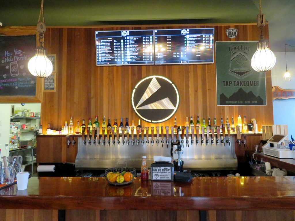 Large bar with a digital beer menu on the back wall and thirty tap handles.