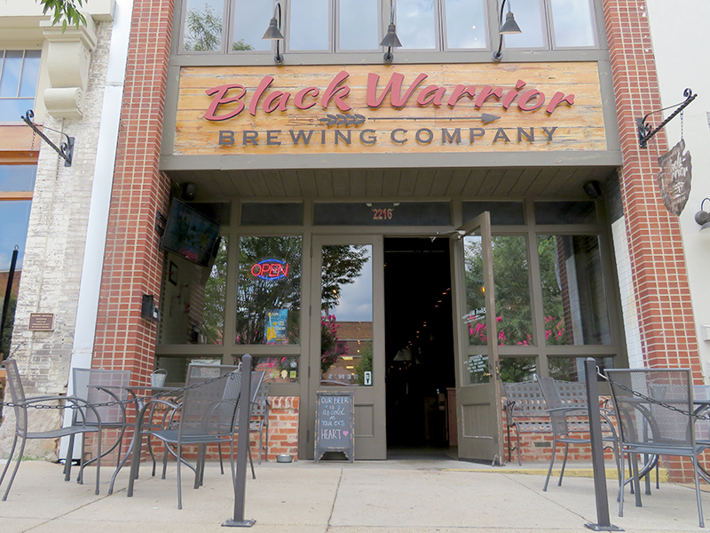 "Brick entrance to a building with large wooden sign overhead that says ""Black Warrior Brewing Company"" above multiple glass windows."