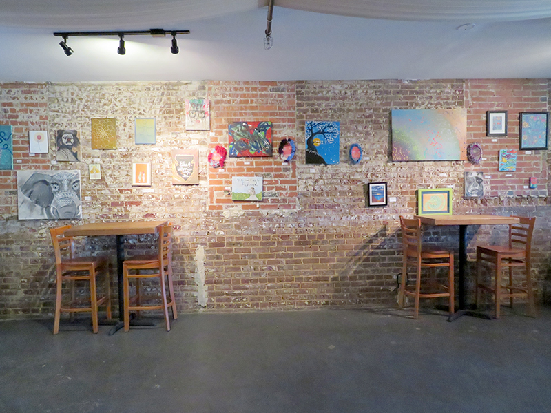 Large, brick wall with multiple pieces of art and two high-top tables with chairs at Black Warrior Brewing.