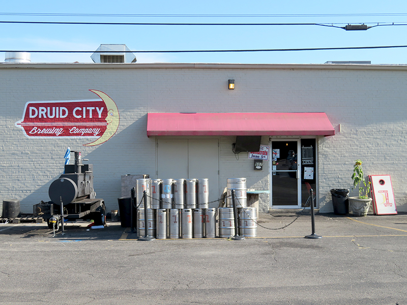 "White brick building with red awning over the doorway with a crescent moon logo to the left that says ""Druid City Brewing Company."""