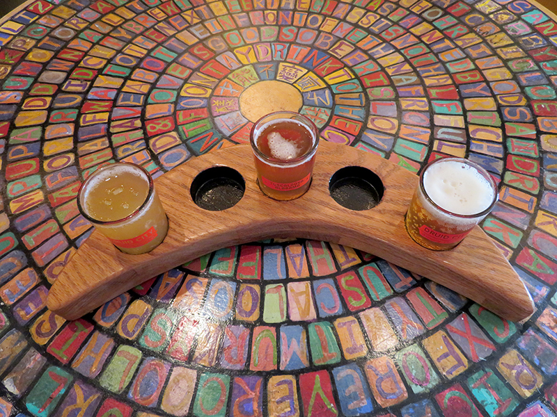 A crescent moon shaped with three tasting glasses full of beer sitting on a colorful table.