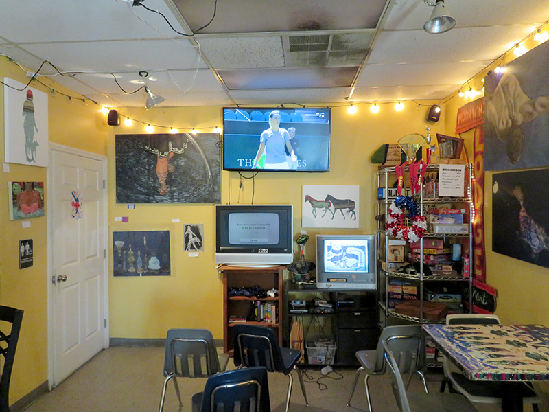 Overview of a seating space with a TV mounted on the wall and various paintings on the wall.