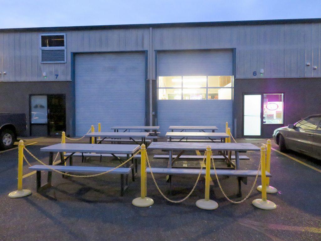 Six plastic picnic tables roped off by yellow chain fence outside of an industrial park building with two large garage doors.