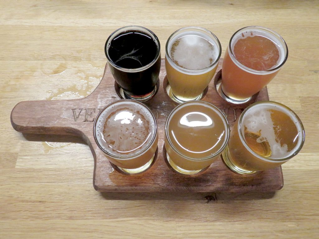 "Rectangular two-by-six flight board with ""Vertigo Brewing"" written across the center with six tasting glasses full of beer."