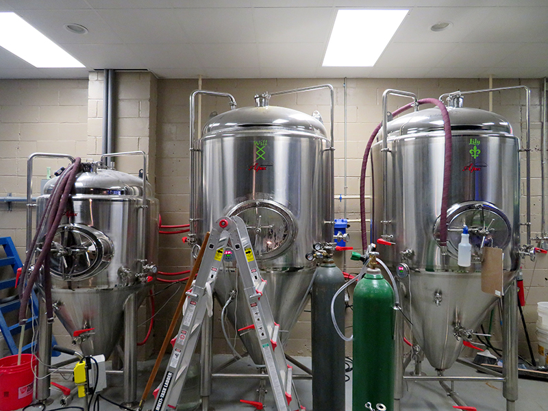 Overview of three fermentation tanks in front of a brick wall at Twisted Barley Brewing.