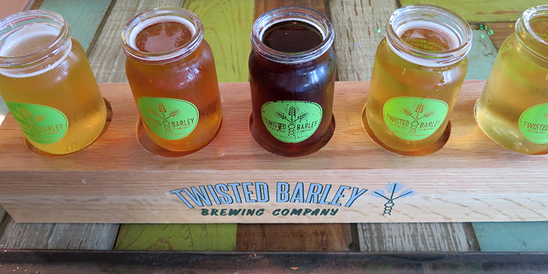 """Overview of a wooden board that says """"Twisted Barley Brewing Company"""" on the front and five tasting glasses full of beer."""