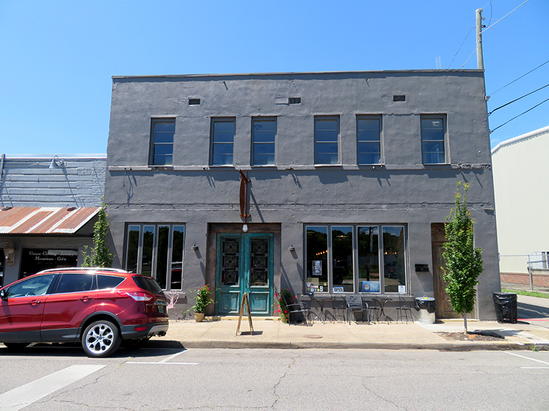 """Overview of a two-story building with green double doors at the entrance below a sign for """"Twisted Barley Brewing Company"""" in jasper, Alabama."""