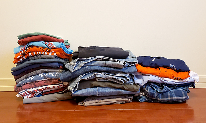 Three stacks of clothes a hardwood floor.