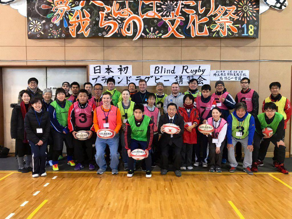 "A group of people stand in front of a banner that says ""blind rugby"" in English and Japanese at the Saitama Prefectural School for the Blind."